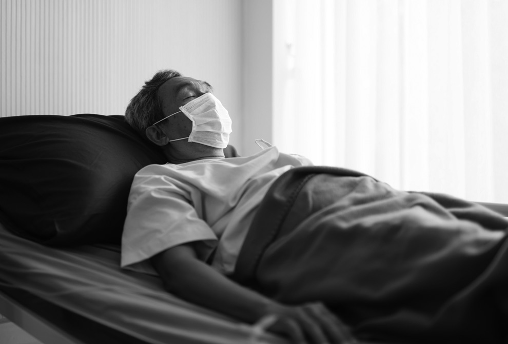 Image of a man laying in bed with a mask on