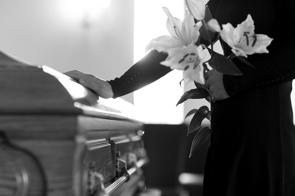 Image of a woman with her hand on a casket, holding white flowers