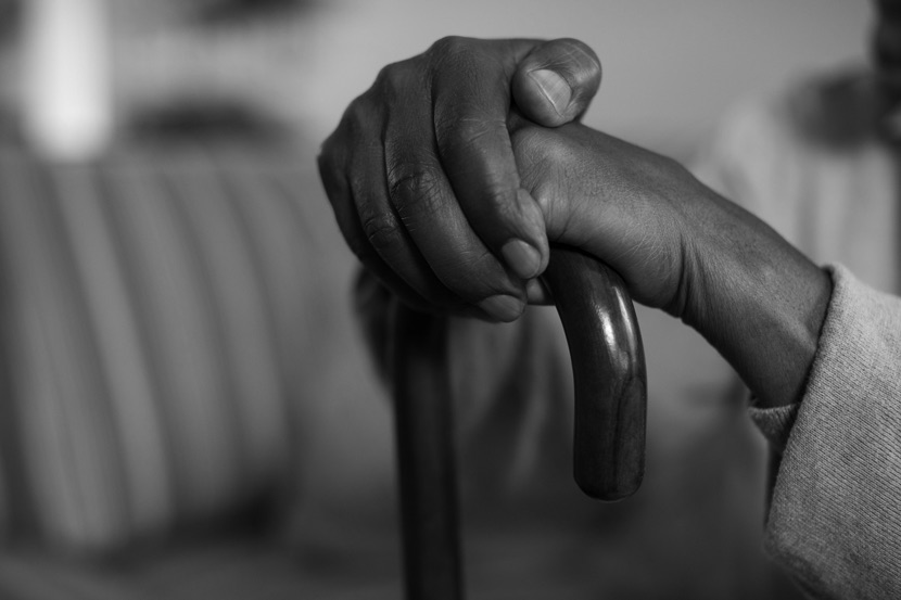 Image of someone with their hands on a cane, close up