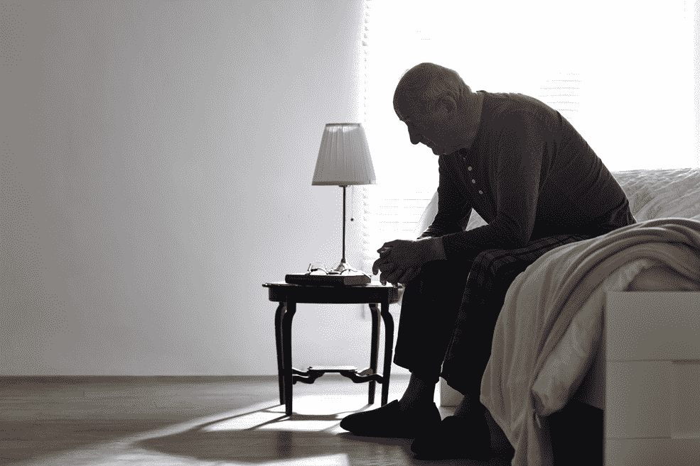 Image of an older man sitting on a bed looking down at the ground sadly